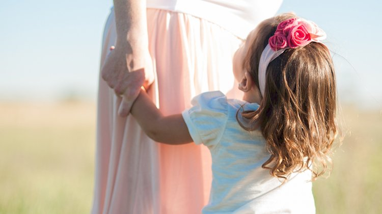 little girl with pink headband looks up at mother holding her hand