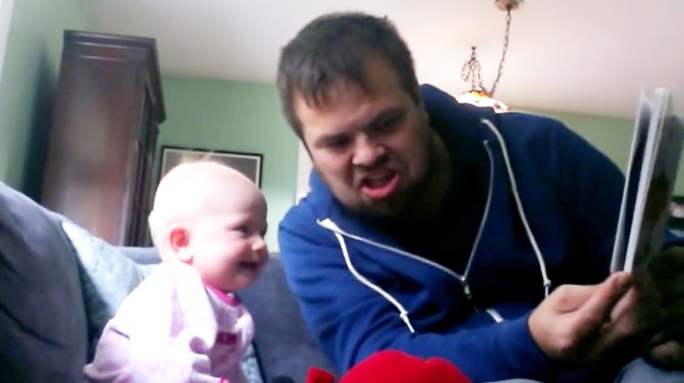 uncle makes funny face while laughing baby looks at book