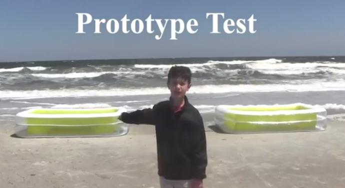 Peytong Robertson on the beach with his prototype sandbags