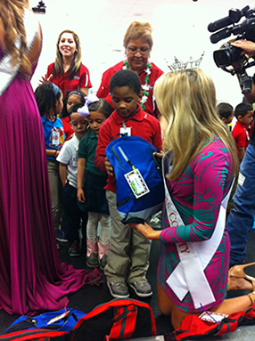 Boy receiving his backpack with joy.