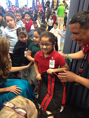 Little girl smiling as she receives her backpack