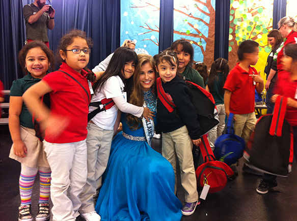 Pageant queen with little girls clinging to her in admiration