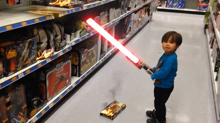 child with lightsaber in toy isle