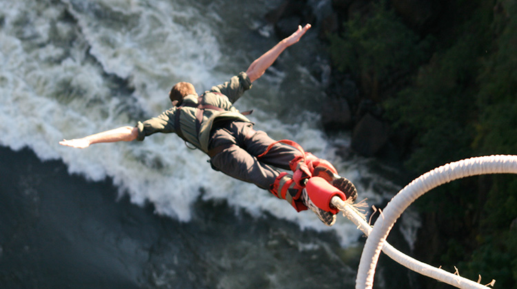 Man bungee jumping over huge cliff