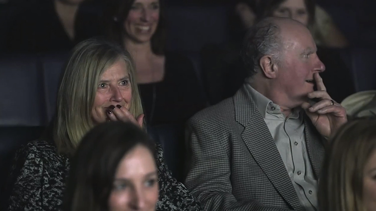 Two grandparents surprised in a dark movie theater