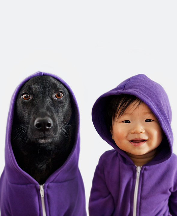 baby and dog wearing matching purple hoodies