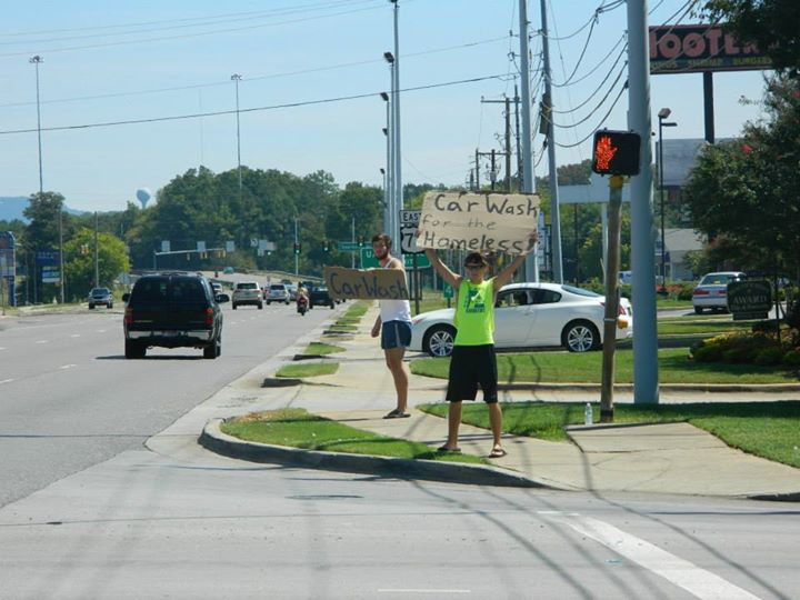 two frat members hold signs for car wash