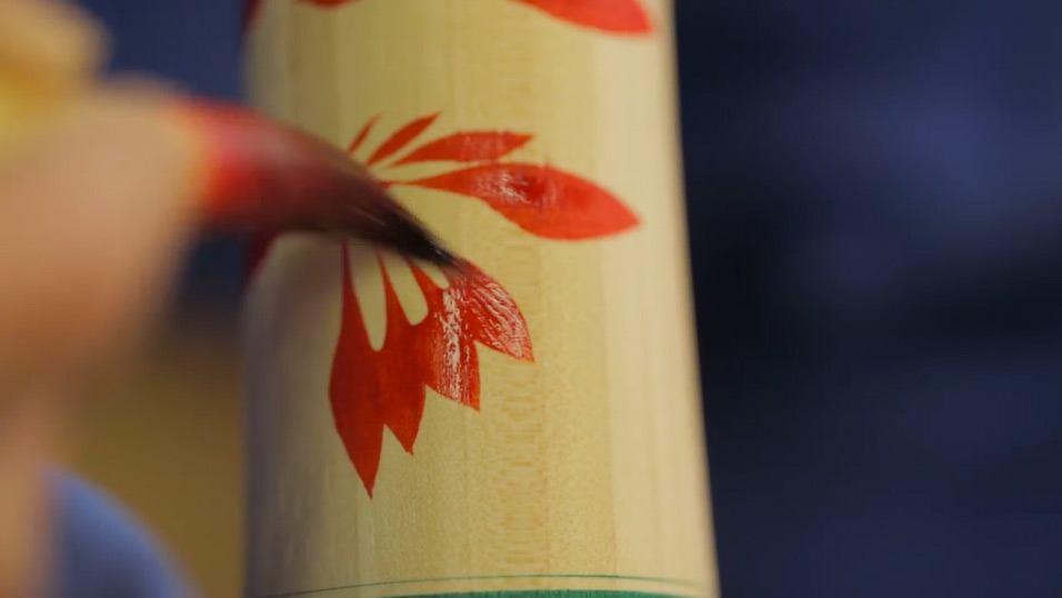 Painting the chrysanthemum pattern onto the body of the doll.