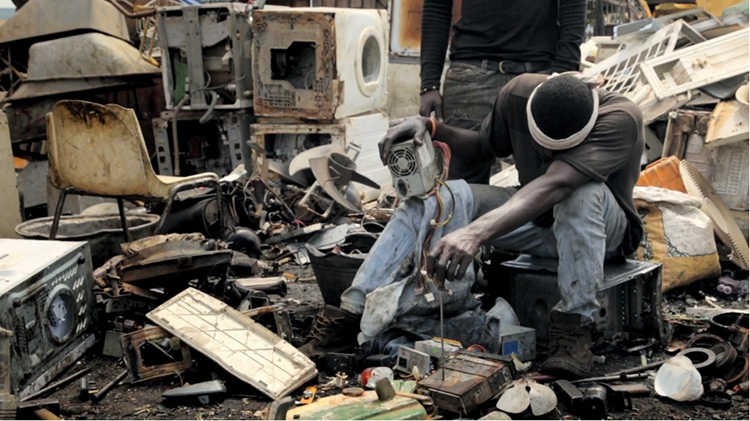 Man in an electronic waste dumping ground.