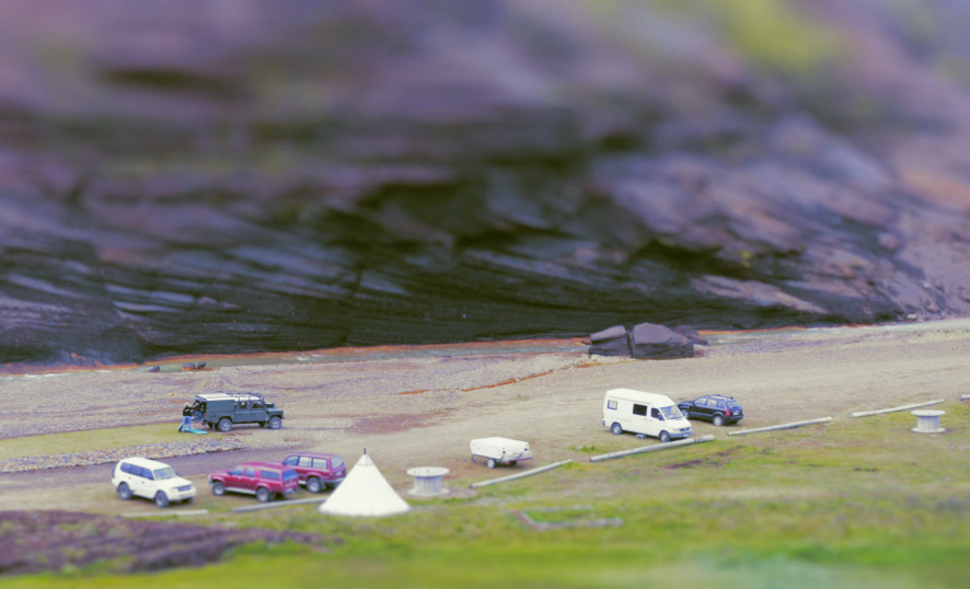 Tilt shift photography perspective of cars from a mountain