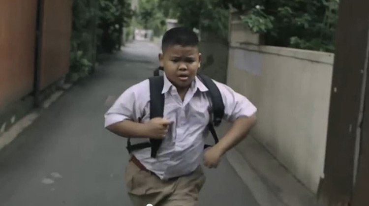 Little kid running to help his mother clean streets