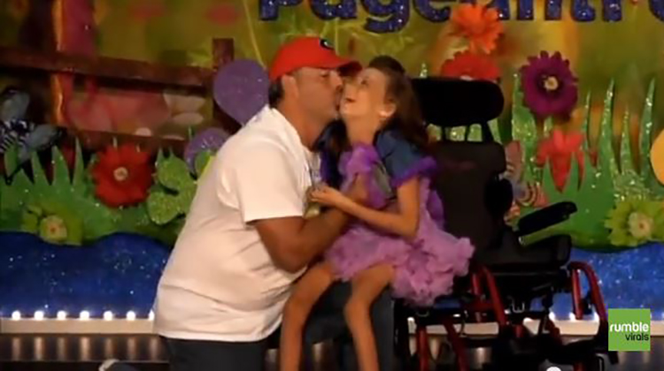 dad kisses his special needs daughter on the cheek