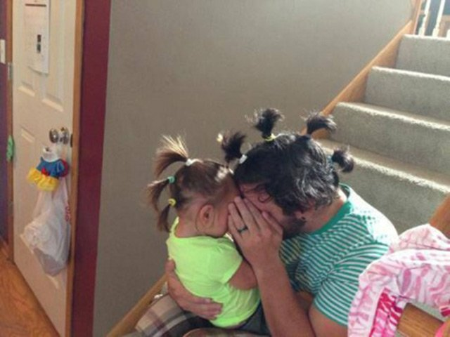 Dad with pigtails playing with daughter