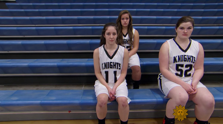 3 girl basketball players sitting in the stands