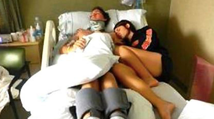 wife lays next to husband on hospital bed