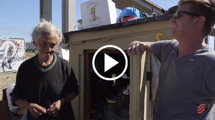 Greg Kloehn with homeless woman and miniature home he built