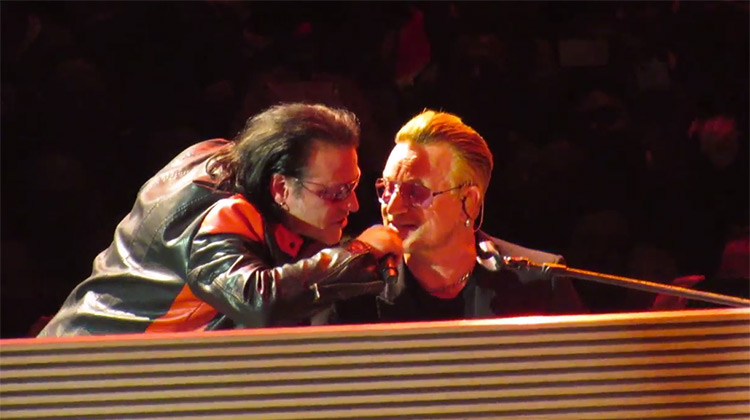 Bono with his impersonator singing at piano in Los Angeles