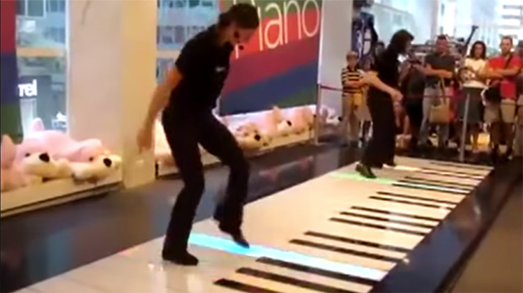Two people playing floor piano