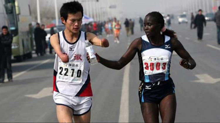 Marathon runner handing water bottle to armless runner