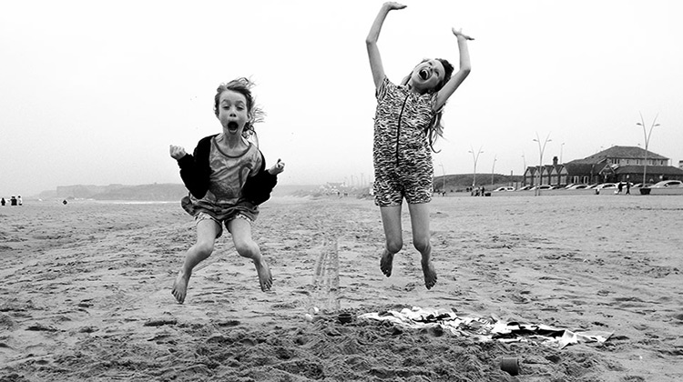 Two girls jumping and smiling on the beach
