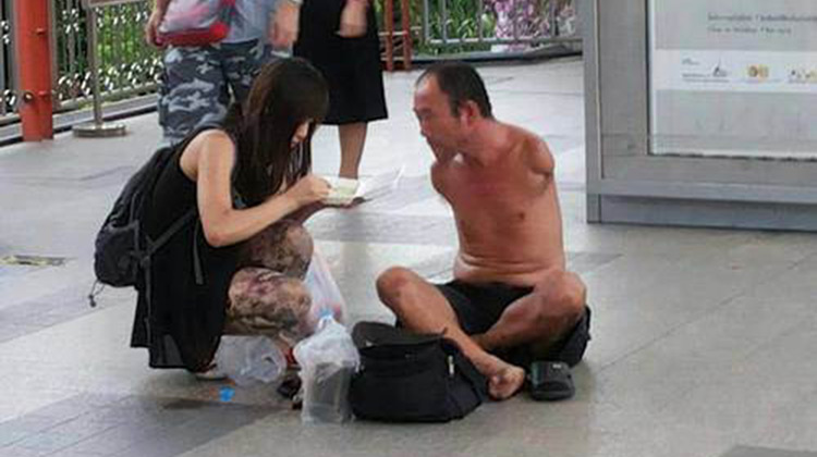 Woman feeding homeless man with no arms