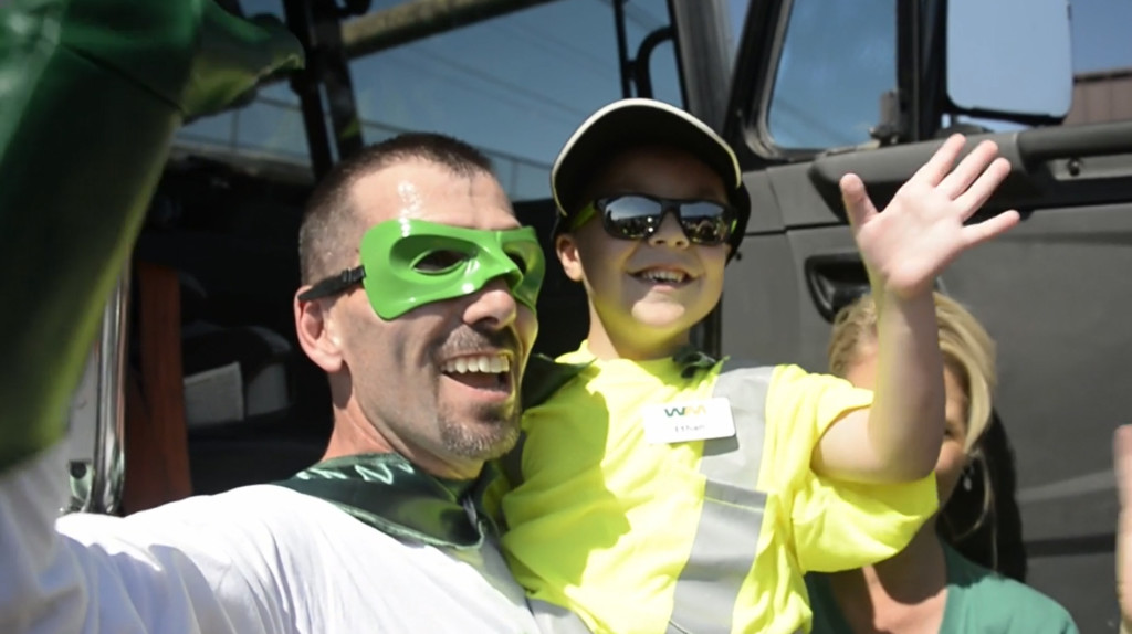 little boy in arms of recycling superhero
