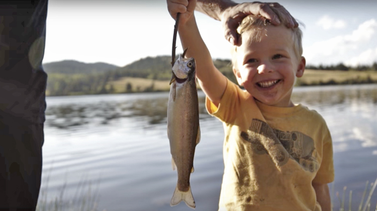 little boy holding up fish he caught with dad's hand resting on head
