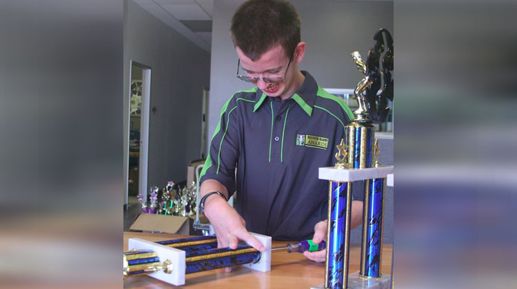 man making trophies in polo