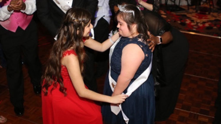 girl in red dress bends down to girl with crown