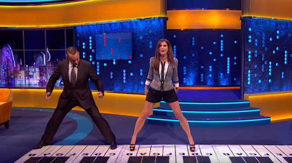 Tom Hanks And Sandra Bullock Stand On Giant Piano Mat