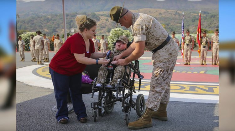 little boy in wheelchair attended by mother and marine