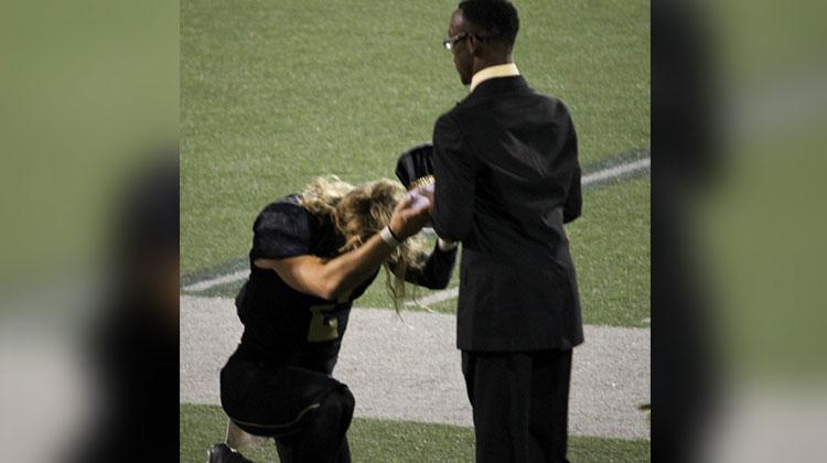 quarterback kneels to present crown to student in black suit