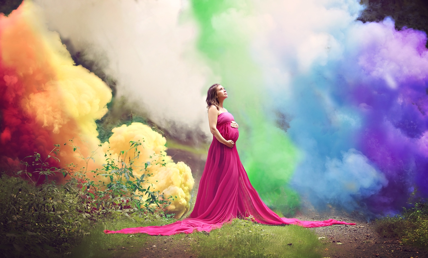 woman in red stands in front of rainbow colored smoke