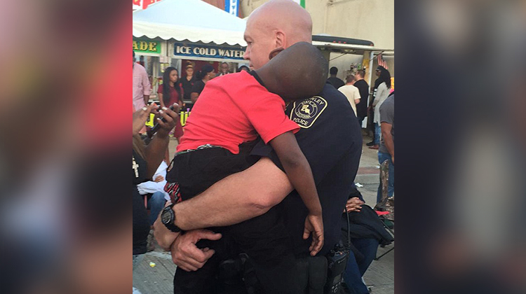 cop carries sleeping child in his arms