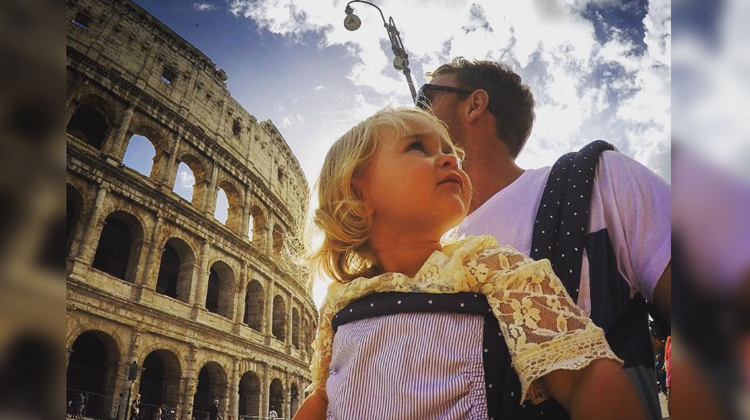 baby carried by dad in front of colisseum