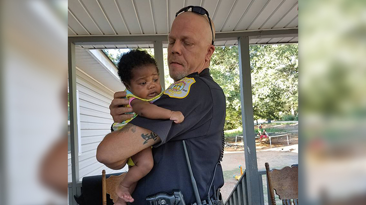 cop holding little infant girl