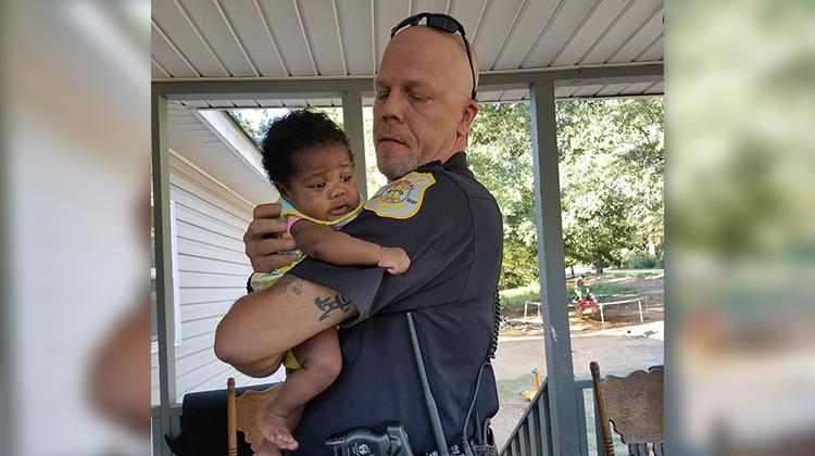 cop holding little infant girl