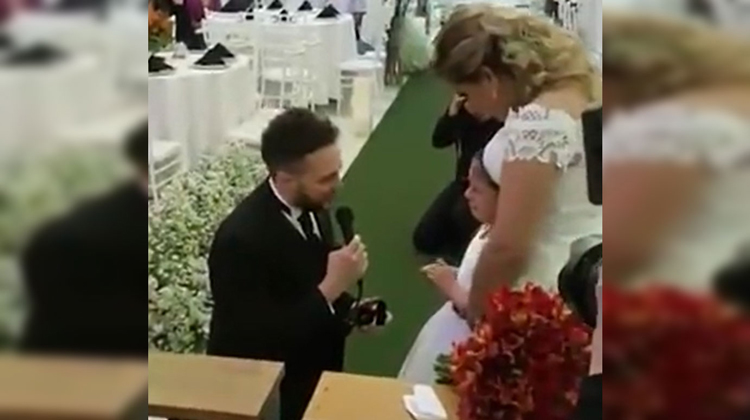 groom kneels toward bride and little girl