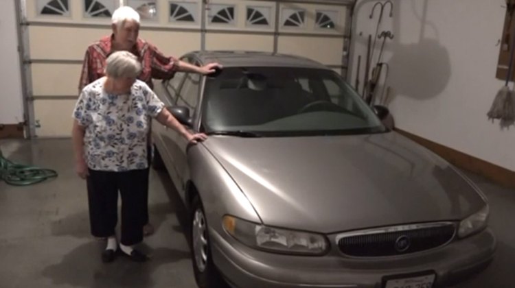 elderly couple by old buick in garage