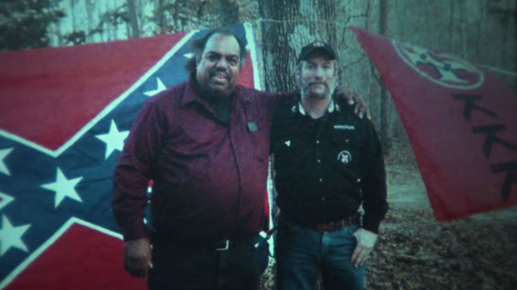 black and white man standing in front of confederate and kkk flags