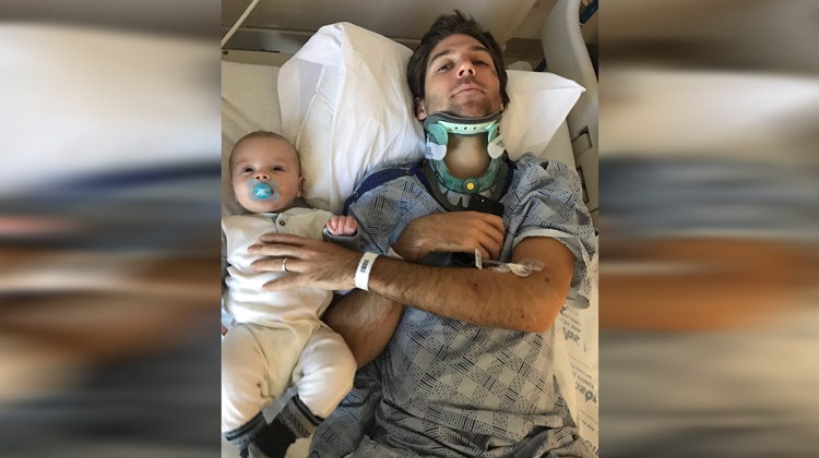 man in neckbrace on hospital bed with baby