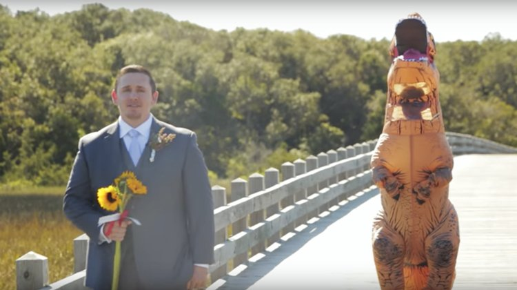 groom with sunflowers with back to woman dressed as trex