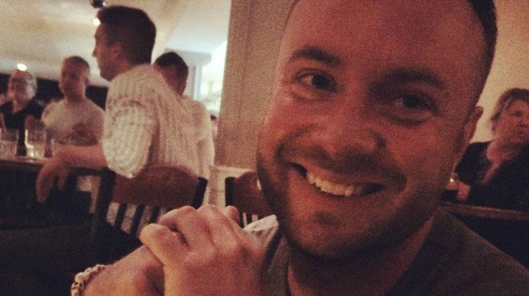 man smiling in dark restaurant