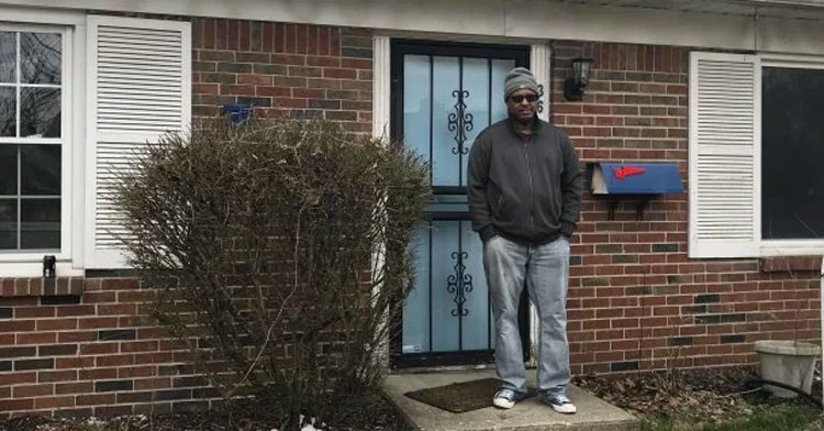 homeless man stands in front of house