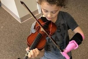 A 5-year-old girl who was born without one arm can now play, thanks to a student at a Texas university who built her an assistive device that allows her to hold her bow.