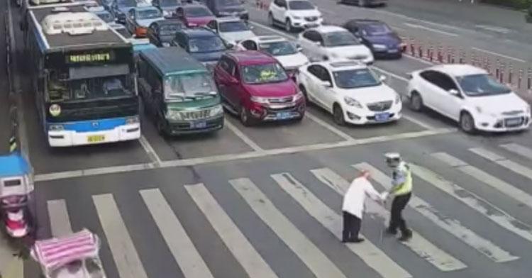 cop helping old man in chinese crosswalk
