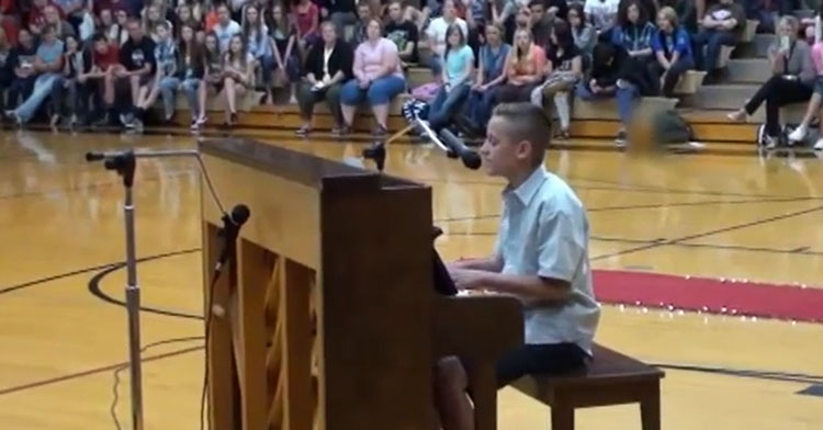 boy playing piano in school gym