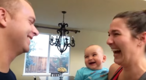 mom dad and baby laughing
