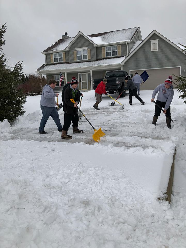 football players shovel snow