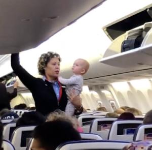 flight attendant holds baby